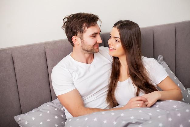 Glückliches paar, das spaß im bett hat. vertraute sinnliche junge paare im schlafzimmer, das sich amüsiert