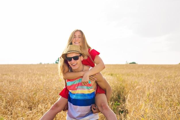 Glückliches paar, das spaß im freien auf dem feld hat