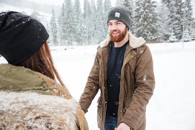Glückliches paar, das spaß im freien mit schnee hat