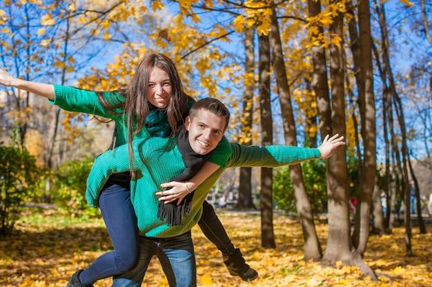 Glückliches paar, das spaß im herbstpark an einem sonnigen falltag hat