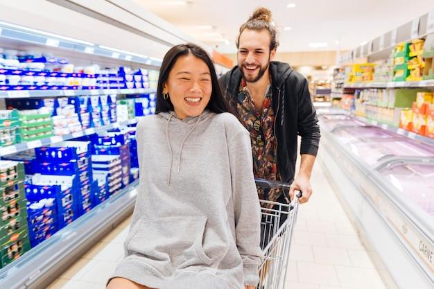 Glückliches paar, das spaß im supermarkt hat