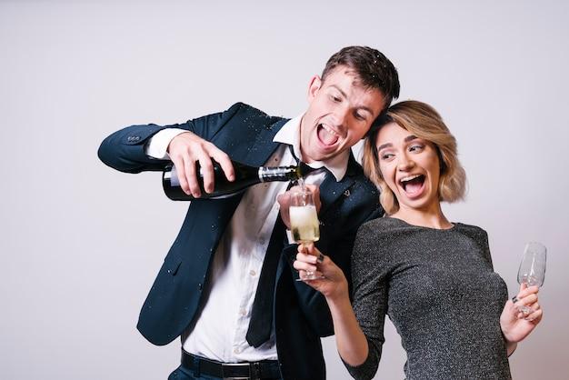 Glückliches paar, das spaß mit champagner hat