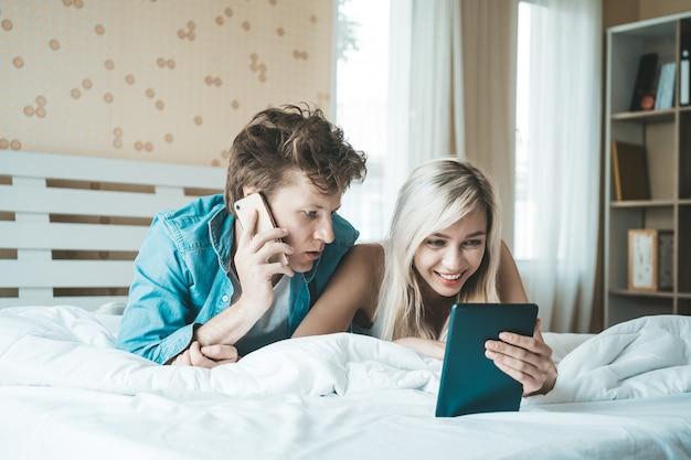 Glückliches paar, das tablet-computer auf dem bett verwendet