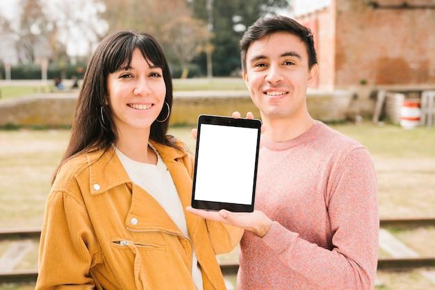Glückliches paar, das tablette auf straße anzeigt
