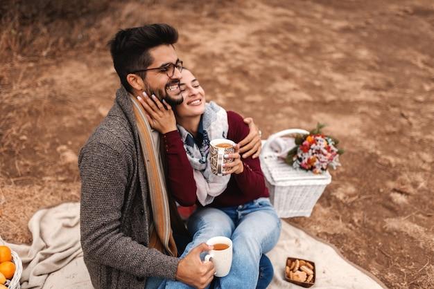 Glückliches paar, das tee auf dem picknick trinkt. frau sitzt im mann