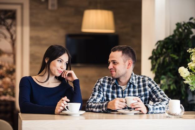 Glückliches paar, das tee und kaffee im café trinkt
