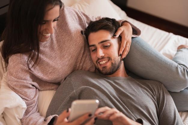 Glückliches paar, das telefon betrachtet
