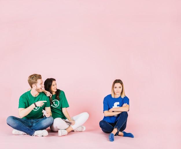 Glückliches paar, das traurige frau auf rosa hintergrund betrachtet
