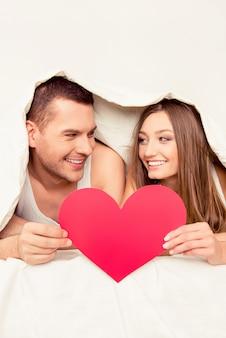 Glückliches paar, das unter decke liegt und gebotspapierherz hält