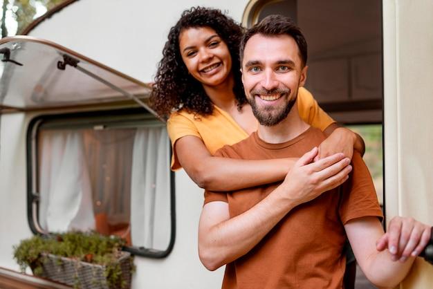 Glückliches paar, das vor wohnmobil steht