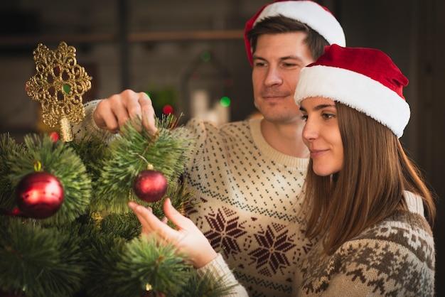 Glückliches paar, das weihnachtsbaum mit kugeln verziert