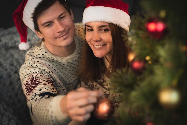 Glückliches paar, das weihnachtsbaum verziert