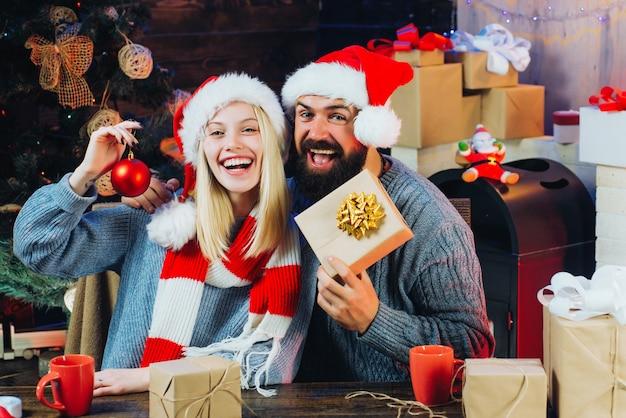 Glückliches paar, das weihnachtsmützen hält, die geschenke drinnen halten