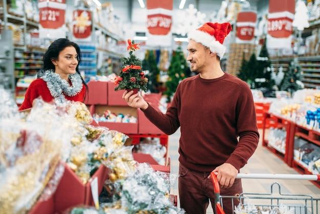 Glückliches paar, das weihnachtssouvenirs im supermarkt kauft