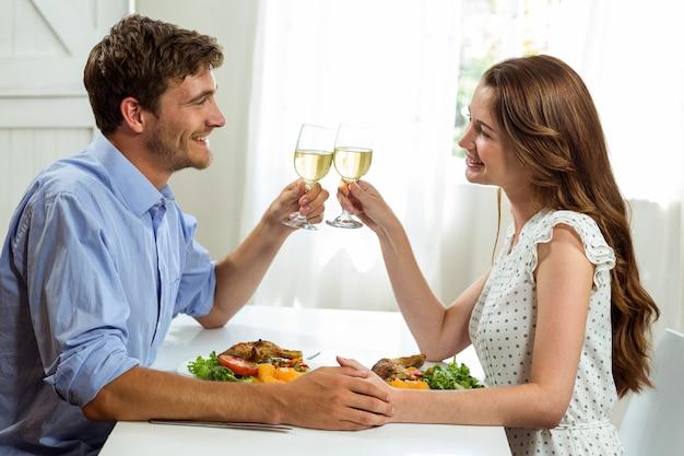 Glückliches paar, das weingläser beim zu mittag essen röstet