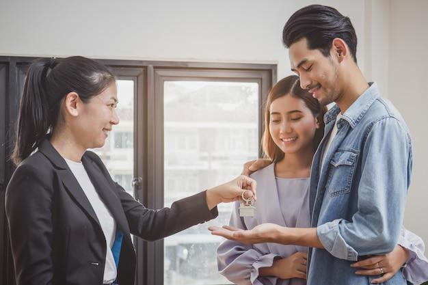 Glückliches paar, das wohnungsschlüssel vom immobilienmakler empfängt