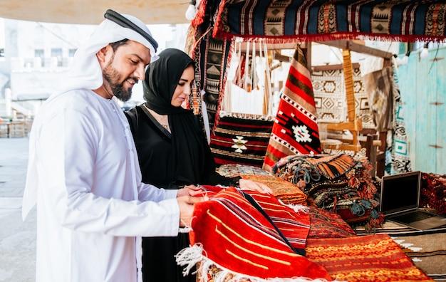 Glückliches paar, das zeit in dubai verbringt. mann und frau tragen traditionelle kleidung beim einkaufen in der altstadt