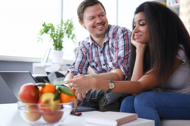 Glückliches paar, das zu hause am tisch auf der couch spricht