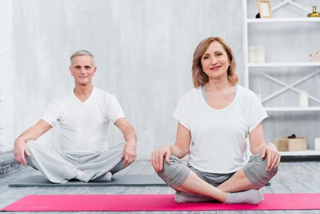 Glückliches paar, das zu hause auf yogamatte sitzt