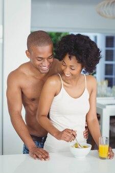 Glückliches paar, das zu hause frühstück in der küche isst
