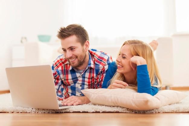 Glückliches paar, das zu hause im internet surft