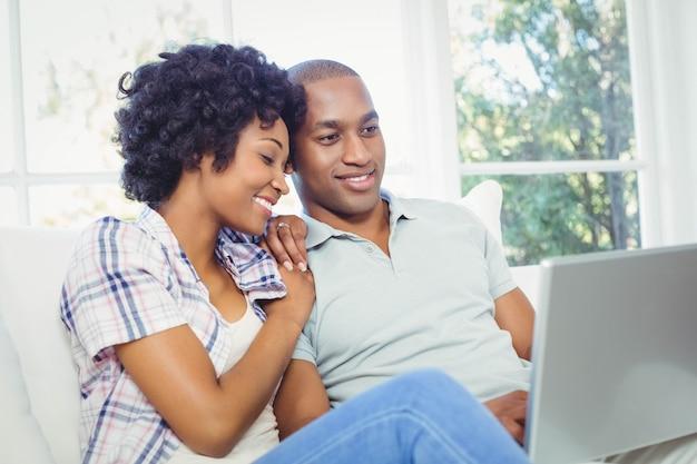 Glückliches paar, das zu hause laptop auf dem sofa verwendet