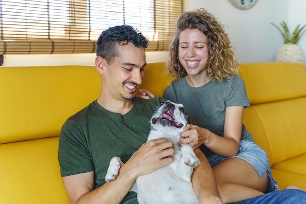 Glückliches paar, das zu hause mit hund spielt. horizontale ansicht des paares, das bulldoggenhaustier auf der couch streichelt.