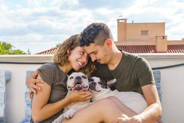 Glückliches paar, das zu hause mit hund spielt. horizontale seitenansicht eines paares, das mit bulldogge auf der couch lacht.
