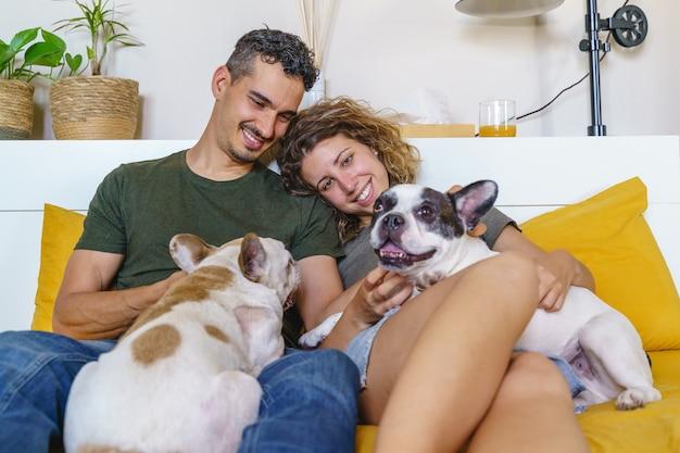 Glückliches paar, das zu hause mit hund spielt. horizontale seitenansicht eines paares, das mit bulldogge im bett lacht.