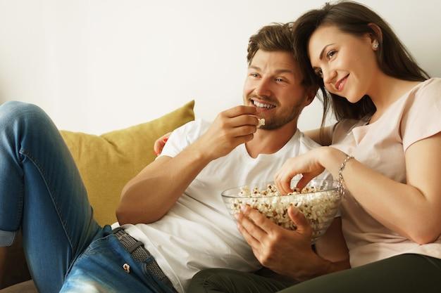 Glückliches paar, das zu hause popcorn isst und film schaut