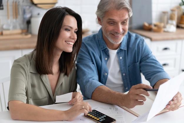 Glückliches paar, das zu hause rechnungen berechnet, eine hypothekenmitteilung erhalten hat, finanzdokumente überprüft