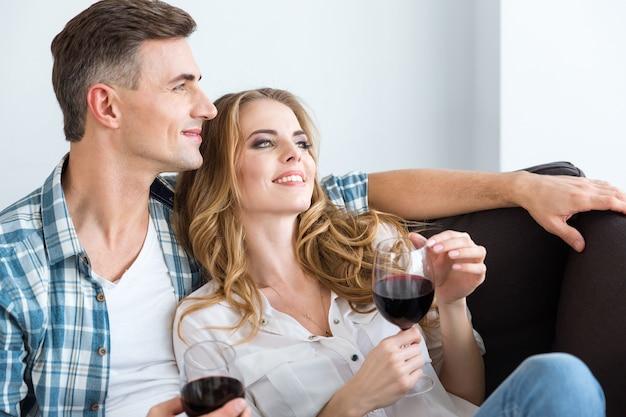 Glückliches paar, das zu hause rotwein sitzt und trinkt