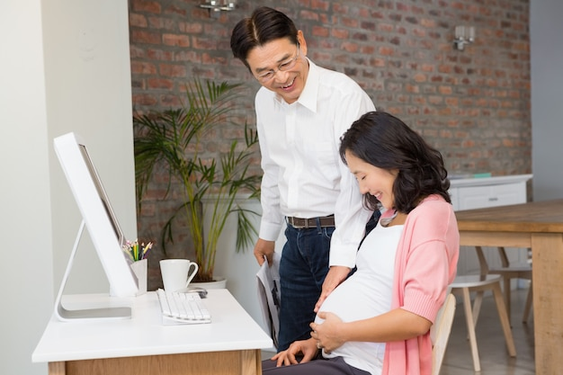 Glückliches paar, das zu hause schwangeren bauch berührt