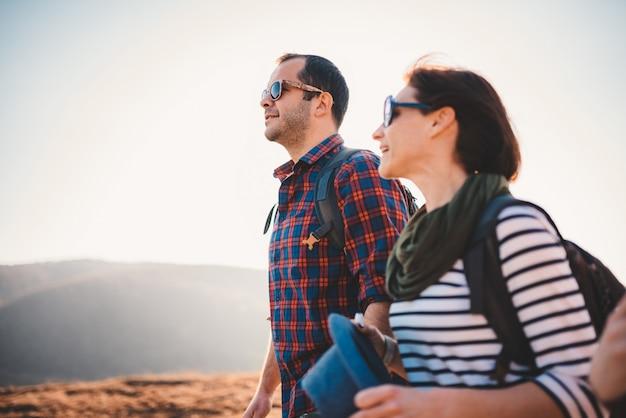 Glückliches paar, das zusammen auf einem berg wandert