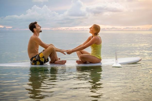Glückliches paar, das zusammen auf paddelbrett bei sonnenuntergang surft