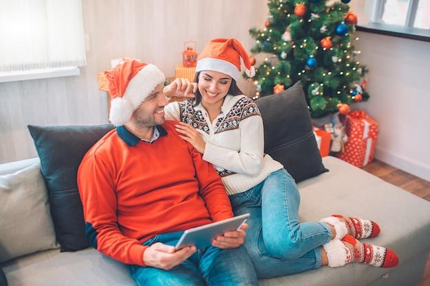 Glückliches paar, das zusammen auf sofa und dem lachen sitzt