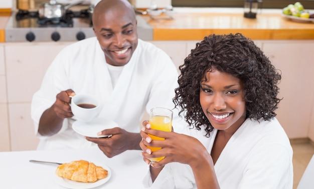 Glückliches paar, das zusammen bei tisch frühstückt