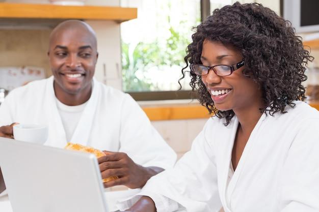Glückliches paar, das zusammen bei tisch unter verwendung des laptops frühstückt