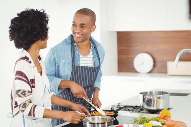 Glückliches paar, das zusammen gemüse kocht