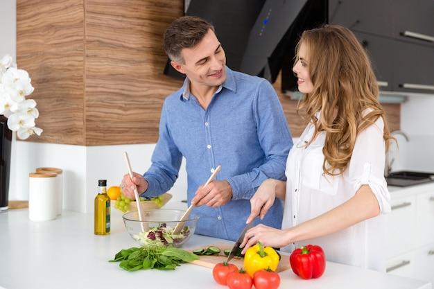 Glückliches paar, das zusammen gemüse schneidet und salat in der küche zubereitet