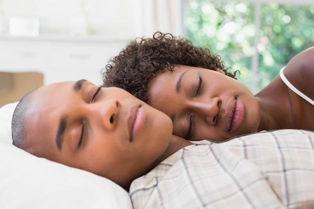 Glückliches paar, das zusammen im bett schläft