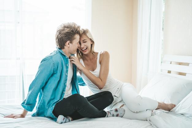 Glückliches paar, das zusammen im schlafzimmer spielt