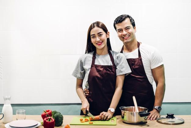 Glückliches paar, das zusammen in der küche kocht und mahlzeit zubereitet