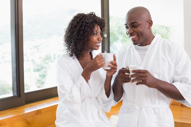 Glückliches paar, das zusammen kaffee in den bademäntel trinkt
