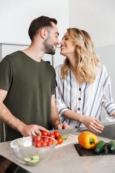 Glückliches paar, das zusammen kocht, während es in der küche steht, gemüse an bord hackt, küssen