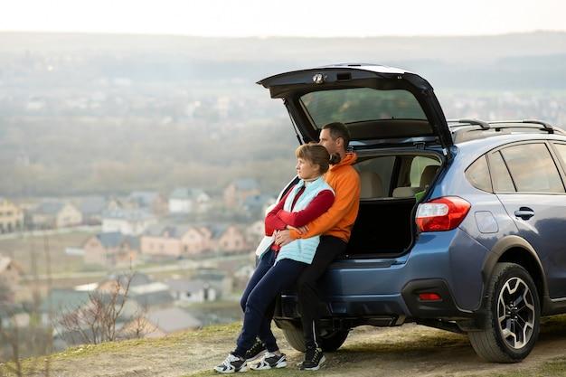 Glückliches paar, das zusammen nahe einem auto mit offenem kofferraum steht und blick auf ländliche landschaftsnatur genießt