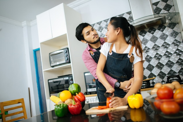 Glückliches paar, das zusammen zu hause in der küche kocht. paar-konzept
