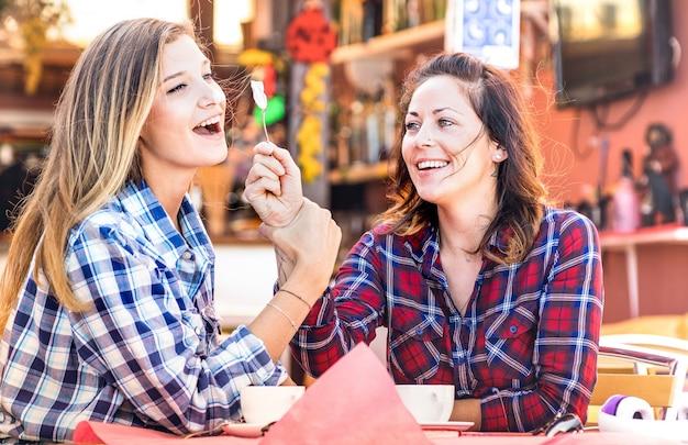 Glückliches paar der freundin, das cappuccino trinkt und zusammen lacht - hangout-konzept mit jungen frauen, die an der kaffeebar sprechen und spaß haben - warmer vintage-filter mit fokus auf das richtige mädchen