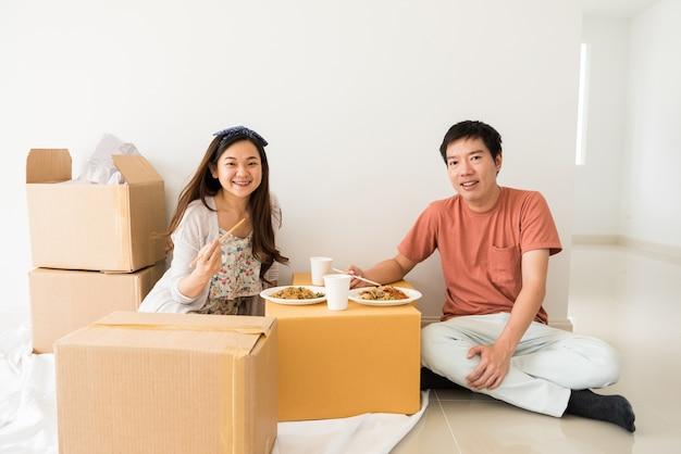Glückliches paar essen nudel auf carboard kasten am neuen haus