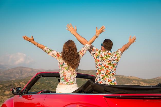 Glückliches paar fährt mit dem auto in den bergen leute, die spaß im roten cabriolet sommerferienkonzept haben